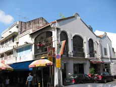 View of Backstage Bar, on the upper floor, proudly displaying the rainbow flag, from the corner of Trengganu and Temple Streets.